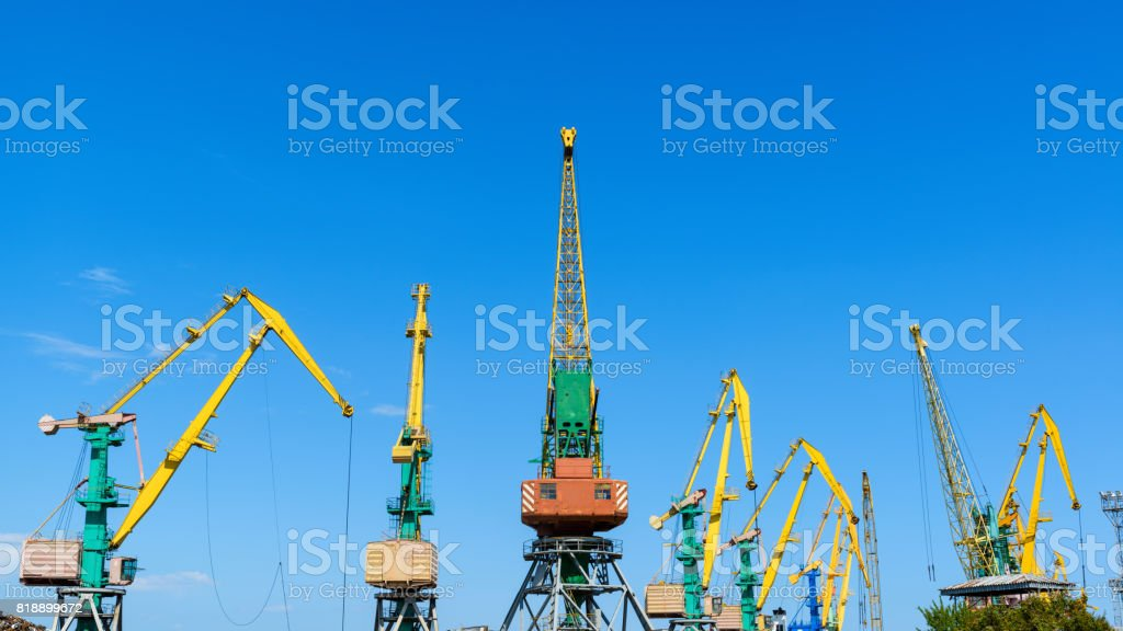Harbor cranes on blue sky background stock photo