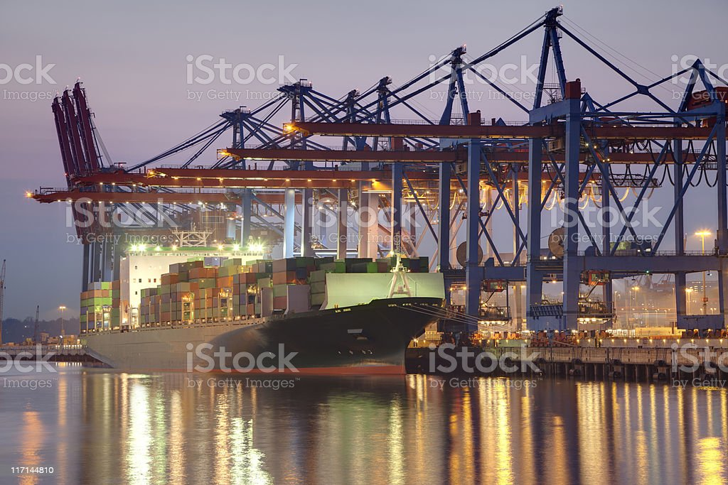 Harbor Hamburg Harbor at night. Photo shows the container terminal with container ship. Business Stock Photo