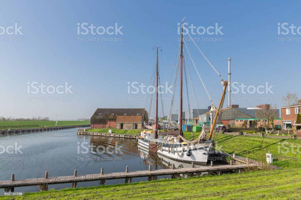 Harbor with wooden sailing vessel in Dutch fishing village Workum stock photo