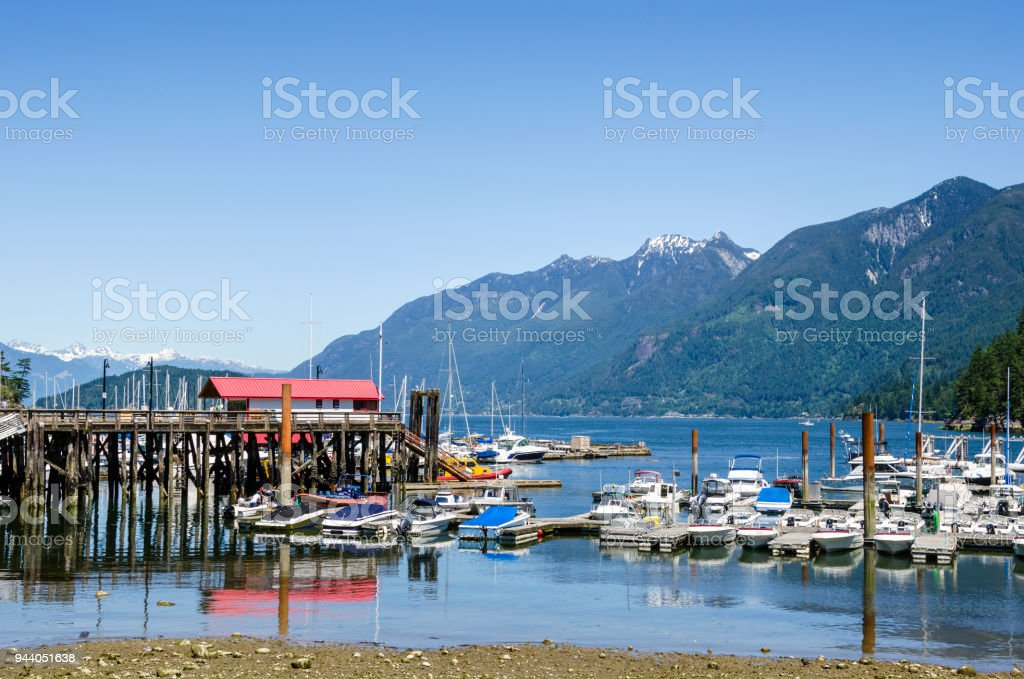 Harbour at Low Tide with Mountain in Background and Blue Sky stock photo