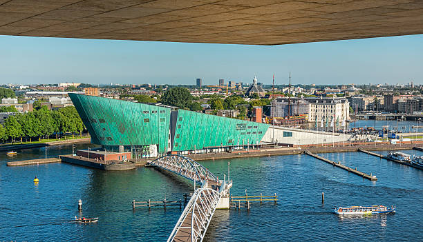 Harbour of Amsterdam with in the front the museum Nemo Amsterdam, the Netherlands - August 23, 2016: New Metropolis museum 'NEMO', science and technology center was build in 1997, Amsterdam gps tagged, seen from the public library nemo museum stock pictures, royalty-free photos & images
