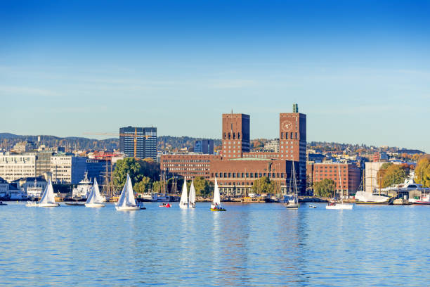 Harbour with boats and wooden yacht Harbour with boats and wooden yacht with town hall on background at sunset in Oslo, Norway oslo stock pictures, royalty-free photos & images