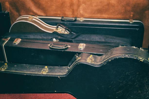 schwere fälle für gitarren sind an der wand - gepäck verpackung stock-fotos und bilder