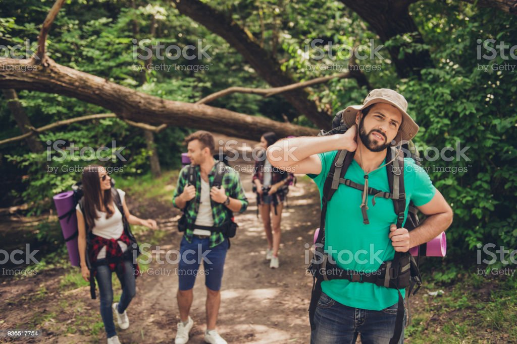 Hard, difficult, tiring and exhausting expedition of four friends in wild forest in trail. Guy is struggling of a neck pain, massaging it stock photo
