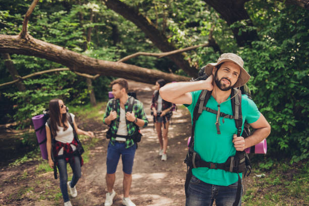 hard, difficult, tiring and exhausting expedition of four friends in wild forest in trail. guy is struggling of a neck pain, massaging it - insect stock pictures, royalty-free photos & images