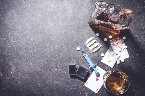 Hard drugs and alcohol on gray stone table stock photo