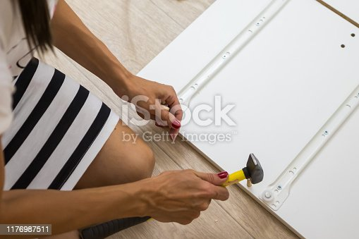 istock Hard hands collect box, close-up. A woman is assembling a white wooden cabinet using a hammer 1176987511