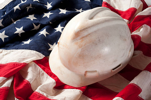 Hard Hat on US Flag Dirty hard hat on American flag to represent labor labor union stock pictures, royalty-free photos & images