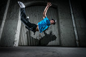 flying young breakdancer at night in front of a depot