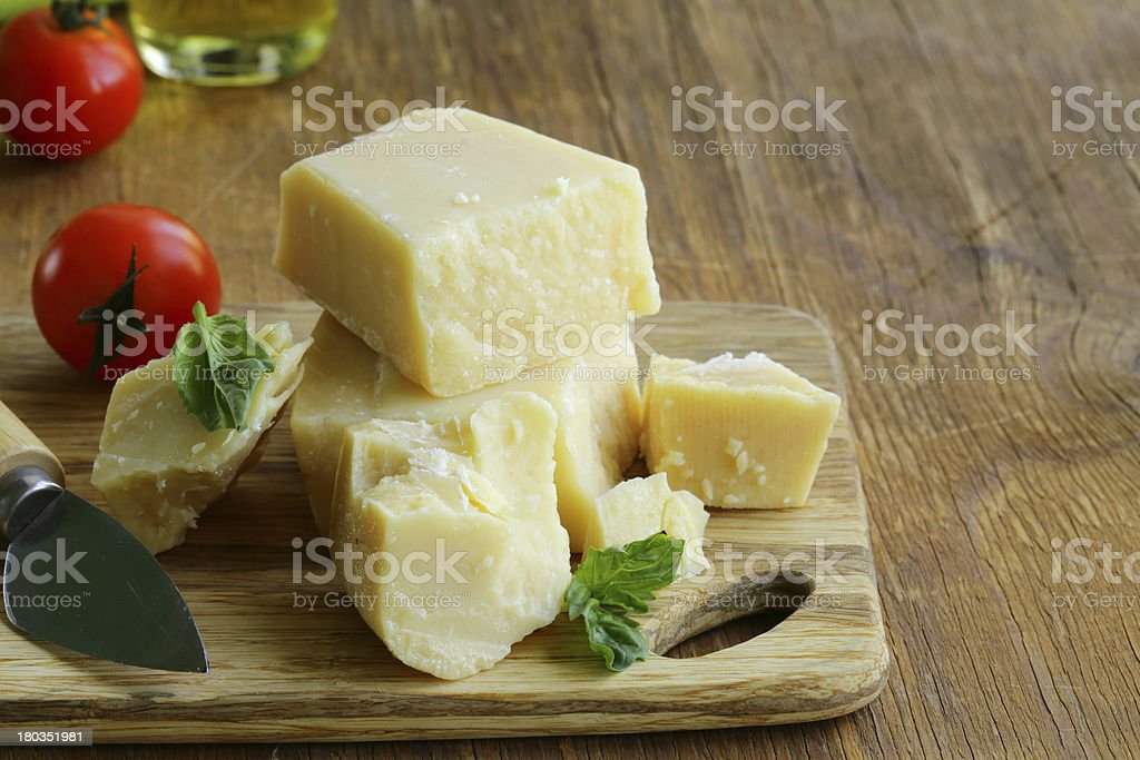 Hard natural parmesan cheese on a wooden board stock photo