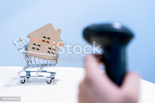 istock Hard paper home model on a cart was scanned by a barcode scanner. a symbol for construction, ecology, loan, mortgage, property or home, business and technology concepts. 940868408