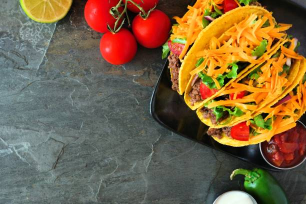 Hard shelled tacos with ground beef, vegetables and cheese, border on a dark background Hard shelled tacos with ground beef, lettuce, tomatoes and cheese. Top view, corner border on a dark background with copy space. taco stock pictures, royalty-free photos & images