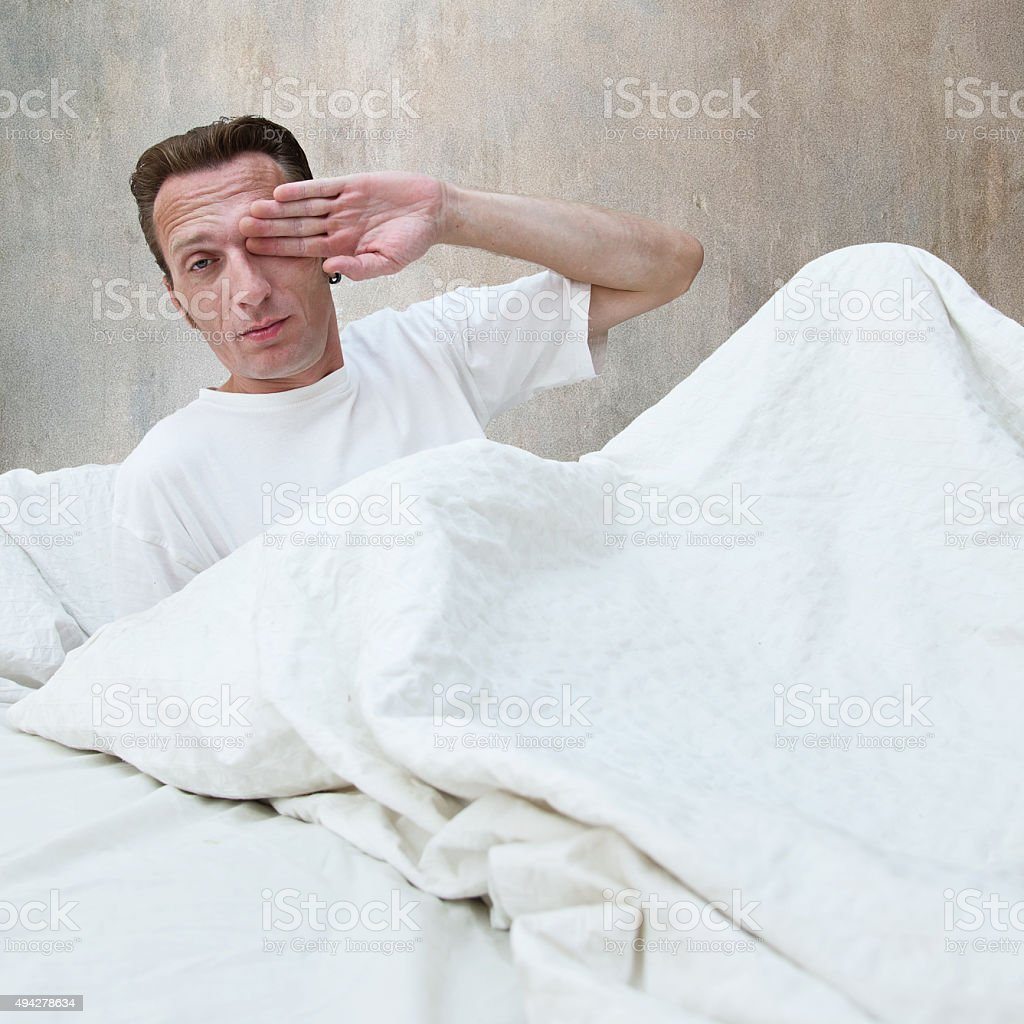 hard wake up. young man in bed. stock photo