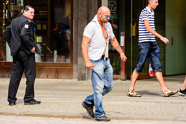 Hard walk Goteborg, Sweden - July 25, 2016: Unknown male walking by on the sidewalk with a very hard and tense style while listening in earphones. Real people in everyday life. men in tight jeans stock pictures, royalty-free photos & images