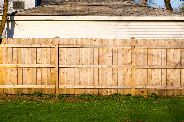 a hard wood fence outside a house - fence stock photos and pictures