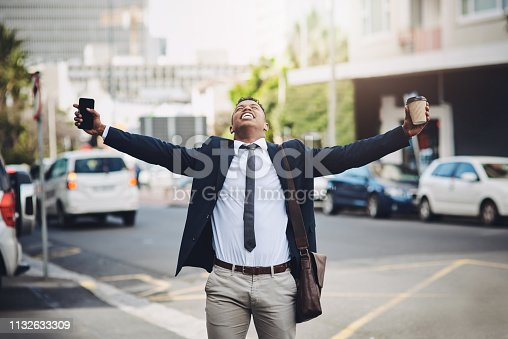 Shot of a happy young businessman standing with his arms outstretched in the city
