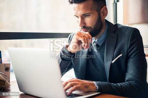 Handsome businessman working on a laptop in a cafe.