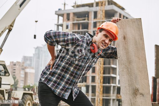 istock Hard work. Construction worker in protective helmet feeling back pain while working at construction site. Building construction. Pain concept 1142818917
