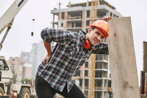 Hard work. Construction worker in protective helmet feeling back pain while working at construction site. Building construction. Pain concept Hard work. Construction worker in protective helmet feeling back pain while working at construction site. Building construction. Pain concept. Dangerous job back pain stock pictures, royalty-free photos & images