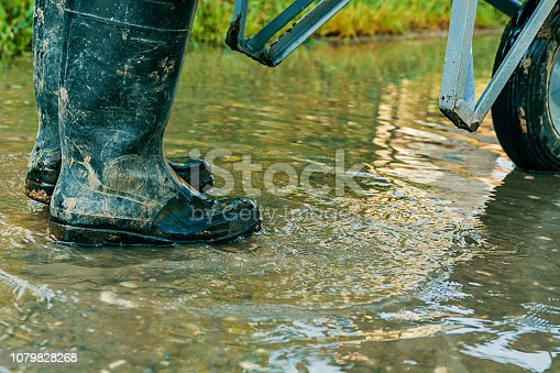 Close View of Man in Dirty Boots Pushing a Trolley Through the Water