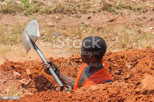 Lusaka, Sambia - November 4, 2010: Hard worker  in Sambia digging up conduit with a shovel in a heat at noontime