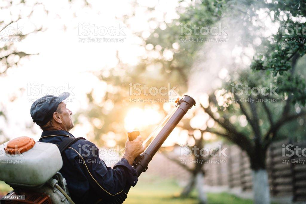hard working handyman using backpack machine for spraying organic pesticides stock photo