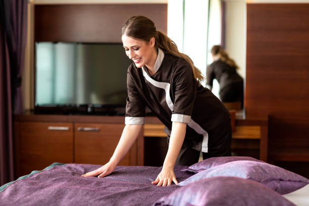 Hard working hotel maid preparing the bed stock photo