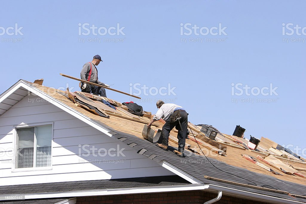 Hard working men on roof stock photo