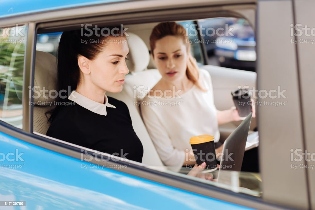 Hard working nice businesswomen working in the car stock photo