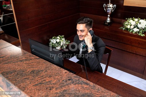 Hard working receptionist talking over phone and managing guest wishes