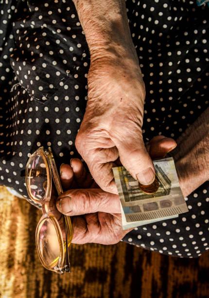 fleiß arbeitende alte frau, die geld in den händen hält. - rentenpunkte stock-fotos und bilder