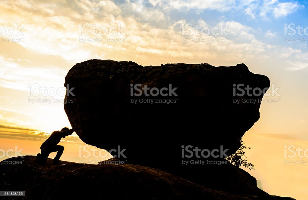 Hard work.The person rolls the rock on mountain. stock photo