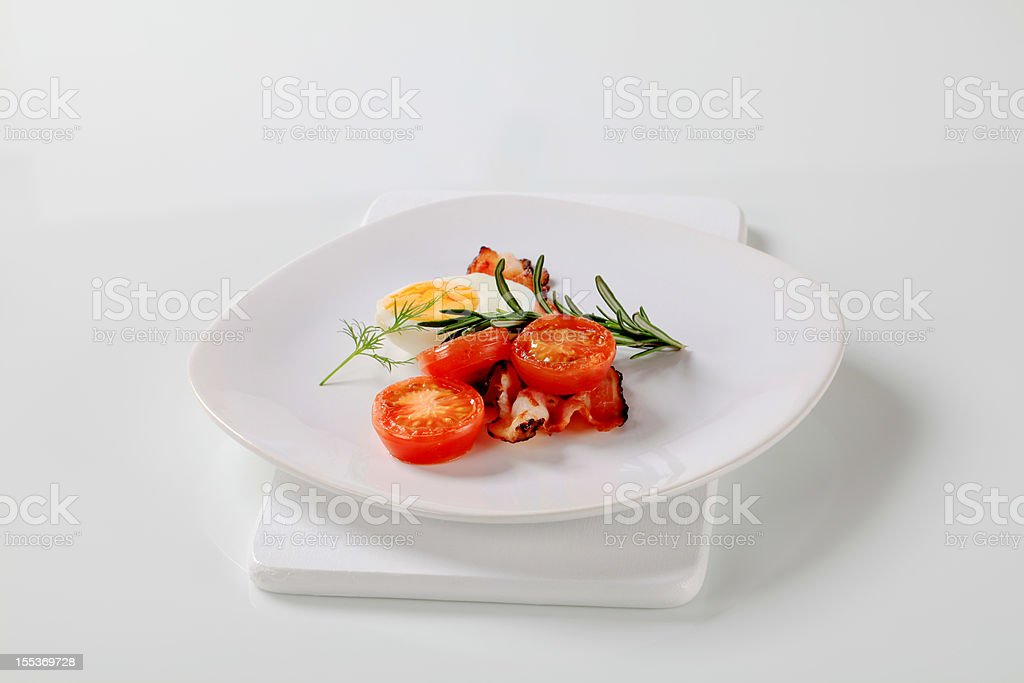 Hardboiled egg, fried bacon and tomato royalty-free stock photo