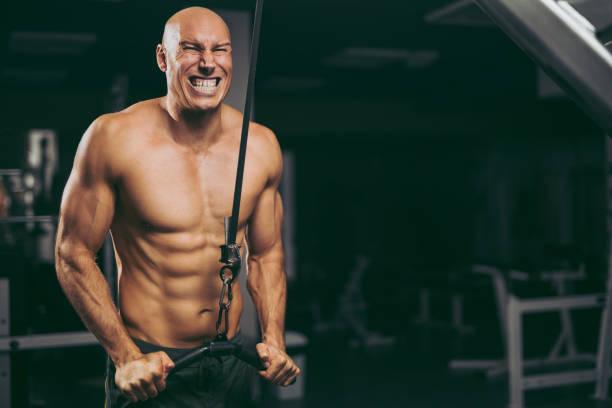 Hardcore workout- bodybuilder exercising using fitness machine stock photo