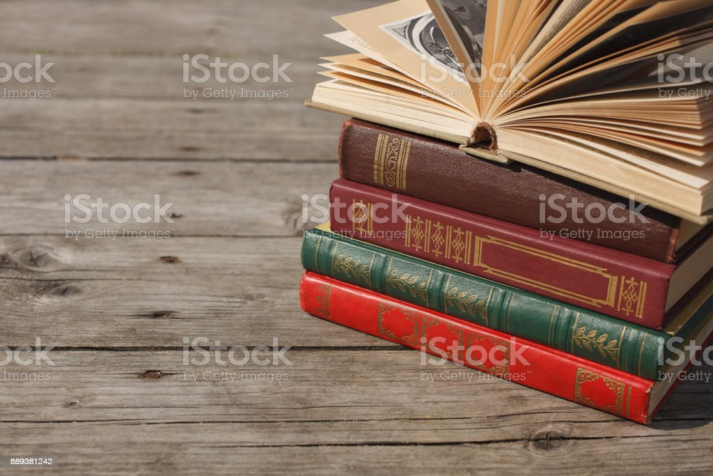 Hardcover books stacked on a wooden floor stock photo