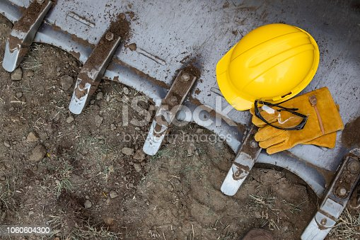 Hardhat, Gloves and Protective Glasses Resting on Bulldozer Bucket Abstract