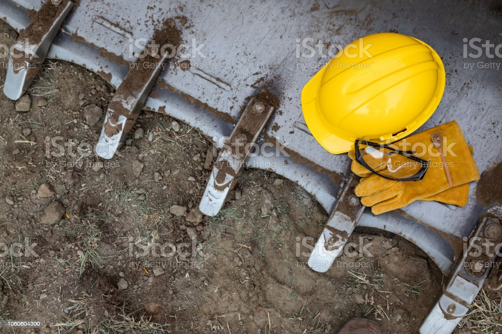 Hardhat, Gloves and Protective Glasses Resting on Bulldozer Bucket Abstract stock photo