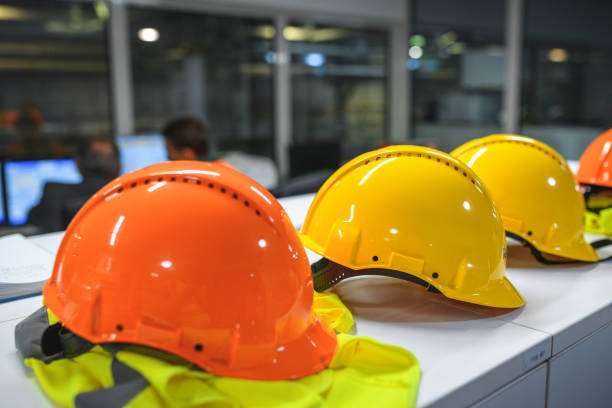 Hardhats Lined Up on Countertop in Recycling Facility Office stock photo
