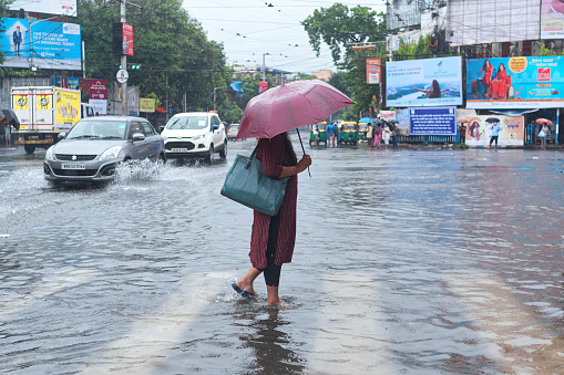 Rashbehari, Kolkata, 09/20/2021: An office going woman walking through flooded street in midst of rain caused by low depression over Bay of Bengal floods several parts of city and adjoining districts causing havoc in everyday life.