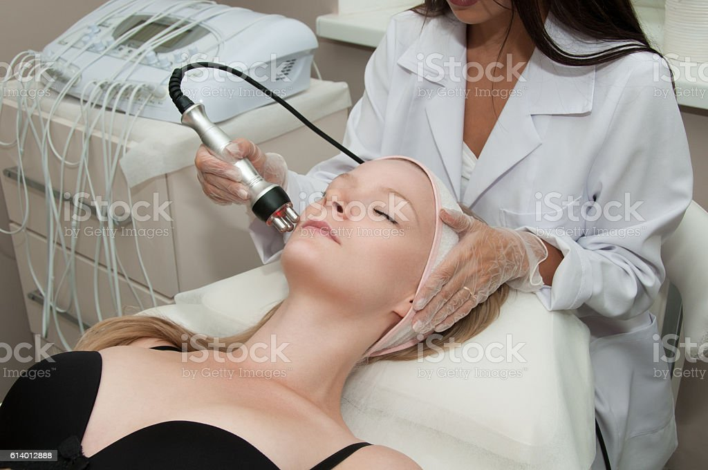 Hardware cosmetology. Young blonde woman getting rf lifting procedure stock photo