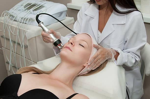 hardware cosmetology. young blonde woman getting rf lifting procedure - frequenzen stock-fotos und bilder