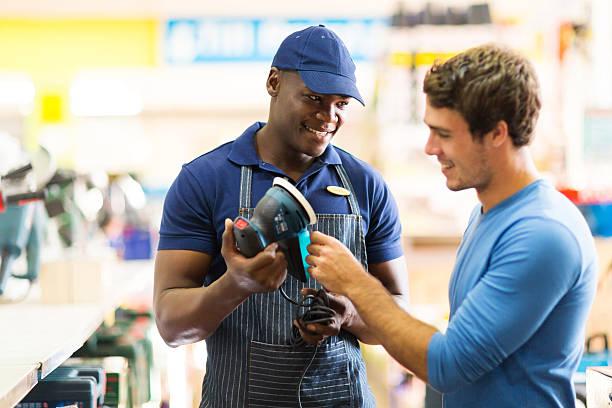 工具店の労働者を示す顧客、サンダー - 小売販売員 ストックフォトと画像