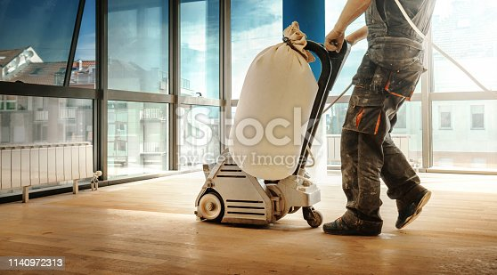 Closeup side view of an unrecognizable handyman using a sanding machine to remove the surface layer of a solid oak hardwood floor in a spacious living room.