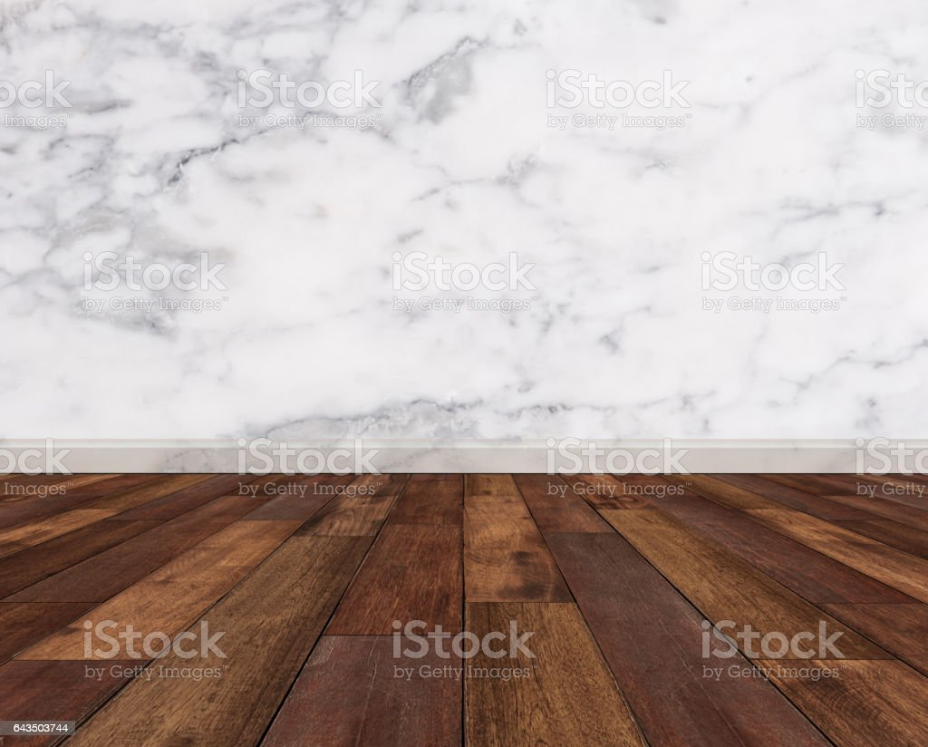 Hardwood floor with white marble wall stock photo