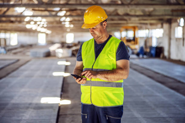 Hardworking blue collar worker standing at construction site and using smart phone to order some more materials for building. stock photo