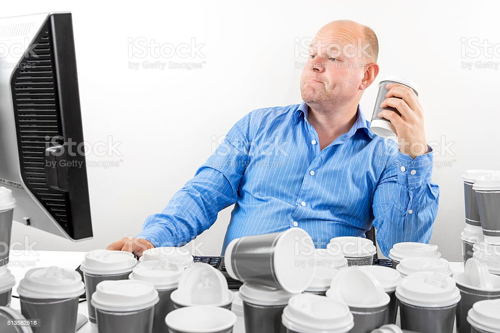 Hardworking business man drinks too much coffee stock photo