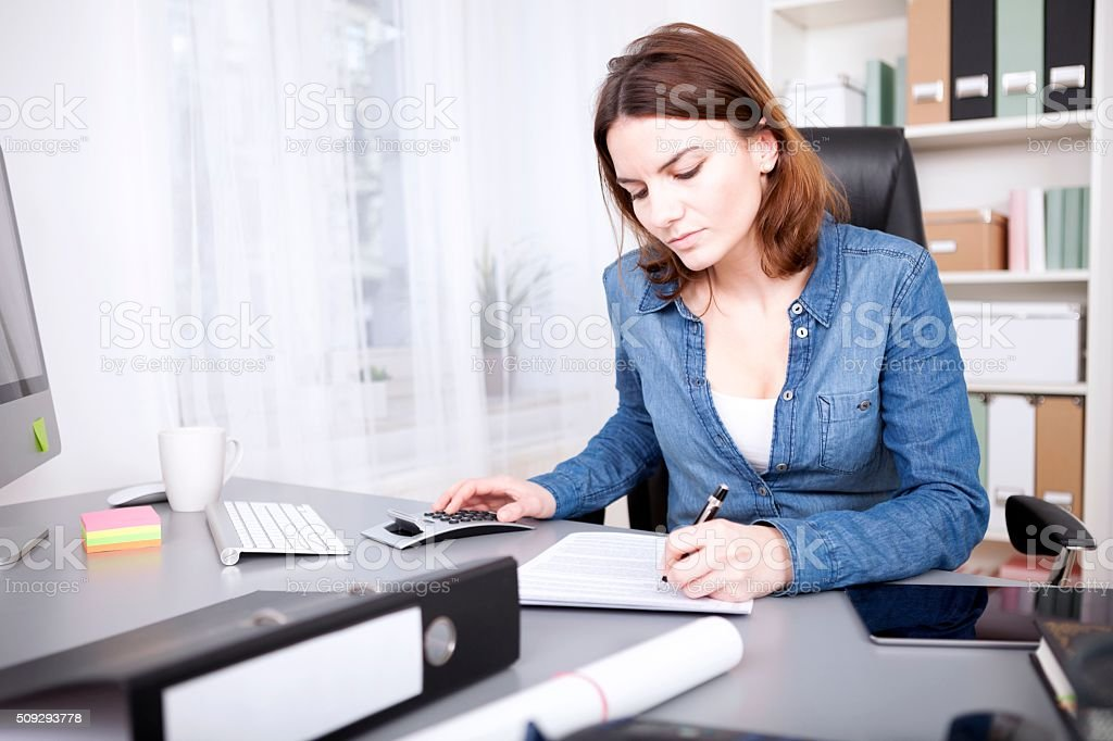 Hardworking businesswoman sitting writing a report stock photo