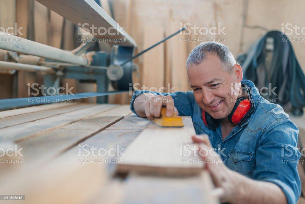 Hardworking carpenter polishing wood using abrasive paper stock photo