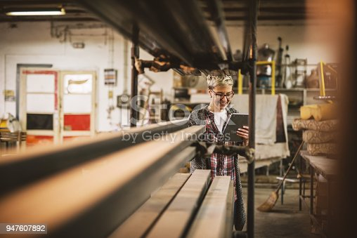 915900234istockphoto Hardworking focused professional motivated business woman holding a tablet next to the shelf with metal pipes in the fabric workshop. 947607892