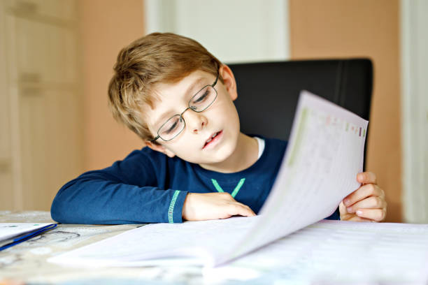 Hard-working happy school kid boy making homework during quarantine time from corona pandemic disease. Healthy child writing with pen, staying at home. Homeschooling concept stock photo